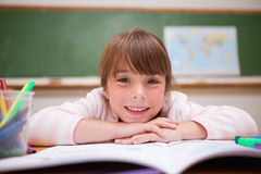 Happy schoolgirl leaning on a desk Stock Photo
