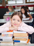 Happy Schoolgirl Leaning On Stacked Books At Desk Royalty Free Stock Photography
