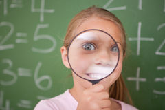 Happy schoolgirl looking through a magnifying glass stock photo