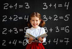 Happy schoolgirl preschool girl with book near school blackboard Stock Photos