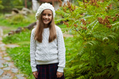 Happy schoolgirl. Pretty blond girl in knitwear standing by green bush in park Royalty Free Stock Photos