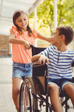 Happy schoolgirl pushing a boy on wheelchair Royalty Free Stock Photography