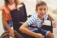 Happy schoolgirl pushing a boy on wheelchair Stock Photo