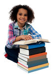 Happy schoolgirl reading a textbook Stock Photo