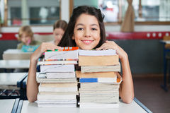 Happy Schoolgirl Resting Chin On Stacked Books At. Portrait of happy little schoolgirl resting chin on stack of books at desk in classroom Royalty Free Stock Photo
