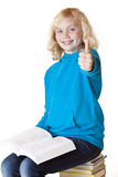 Happy schoolgirl sitting on books showing thumb Royalty Free Stock Images