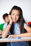 Happy Schoolgirl Sitting At Desk In Classroom royalty free stock photography