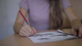 Happy schoolgirl sitting at desk and writing in exercise book stock video footage