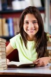 Happy Schoolgirl Sitting At Table In Library Royalty Free Stock Photo