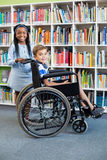 Happy schoolgirl standing with schoolboy on wheelchair. Portrait of schoolgirl standing with schoolboy on wheelchair in library stock photos