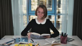 A happy schoolgirl takes the book from the table and starts reading it. Doing homework. Smiling at the camera stock footage