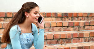 Happy schoolgirl talking on mobile phone stock video footage
