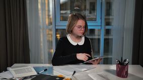 A happy schoolgirl uses a tablet. Looks for information on the Internet. does the homework. stock video footage