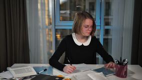 Happy schoolgirl uses a tablet. Writes in a notebook doing homework. stock video footage