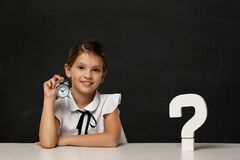 Free Happy Schoolgirl With Alarm Clock Sitting At Table Royalty Free Stock Photos - 217098038