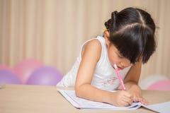 Happy schoolgirl works on her homework
