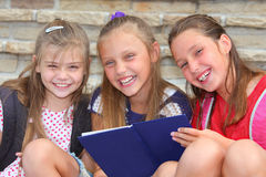Happy schoolgirls. With backpacks and book sitting on stairs stock images