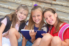 Happy schoolgirls. With backpacks and book sitting on stairs royalty free stock images