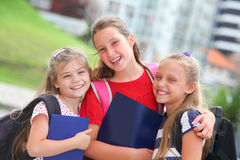 Happy schoolgirls with backpacks. Outdoors royalty free stock photos