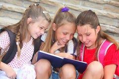 Happy schoolgirls reading a book. Happy schoolgirls sitting on the stairs reading a book royalty free stock image