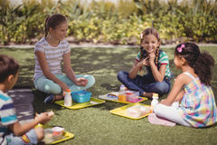 Happy schoolkids interacting while having meal in schoolyard. At school Stock Image