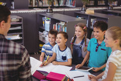 Happy schoolkids interacting with teacher in library. At school Royalty Free Stock Images