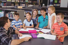 Happy schoolkids interacting with teacher in library. At school Royalty Free Stock Photography