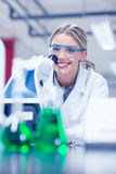 Happy science student working with microscope in the lab Stock Photography