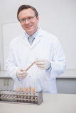 Happy scientist holding kernel in tube Stock Images