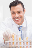 Happy scientist looking at camera with tubes of corn and kernel Stock Images