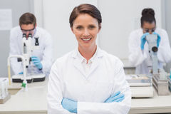 Happy scientist smiling at camera with arms crossed. In the laboratory Stock Images