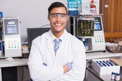Happy scientist smiling at camera with arms crossed. In the laboratory Stock Image