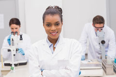 Happy scientist smiling at camera with arms crossed. In the laboratory Royalty Free Stock Image