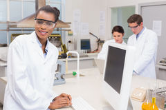 Happy scientist smiling at camera while colleagues working together Stock Photography