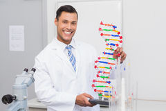 Happy scientist smiling at camera with DNA helix Stock Photos