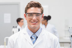 Happy scientist smiling at camera with protective glasses Royalty Free Stock Photo