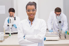 Happy scientist smiling at camera with protective glasses. In the laboratory Royalty Free Stock Photo