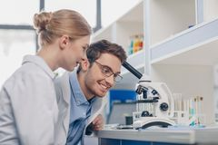 Scientists working with microscope. Happy scientists in white coats working with microscope in laboratory Stock Photo