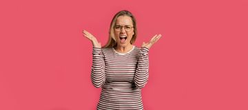 Happy screaming blond woman, isolated with wide opened hands royalty free stock photo