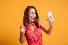 Happy screaming brunette woman in dress making selfie on smartphone. Over yellow background Royalty Free Stock Image