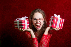 Happy screaming girl in red dress with two gift boxes Stock Photos
