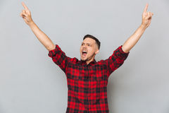 Happy screaming man pointing up. Happy screaming man in shirt pointing up and looking away over gray background royalty free stock photo