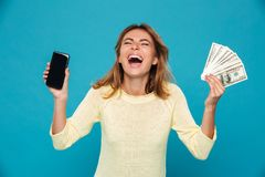 Happy screaming woman in sweater showing blank smartphone screen. And holding money over blue background Royalty Free Stock Images