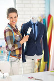 Happy seamstress cleaning suit on mannequin Stock Images