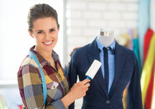 Happy seamstress cleaning suit on mannequin Stock Image