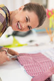 Happy seamstress cutting fabric Stock Image