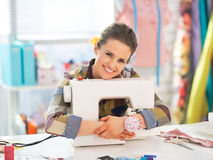 Happy seamstress embracing sewing machine Royalty Free Stock Image