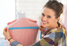 Happy seamstress measuring garment on mannequin Royalty Free Stock Photography