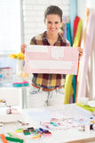 Happy seamstress showing pattern in studio Royalty Free Stock Photo