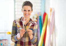 Happy seamstress showing scissors Stock Photo